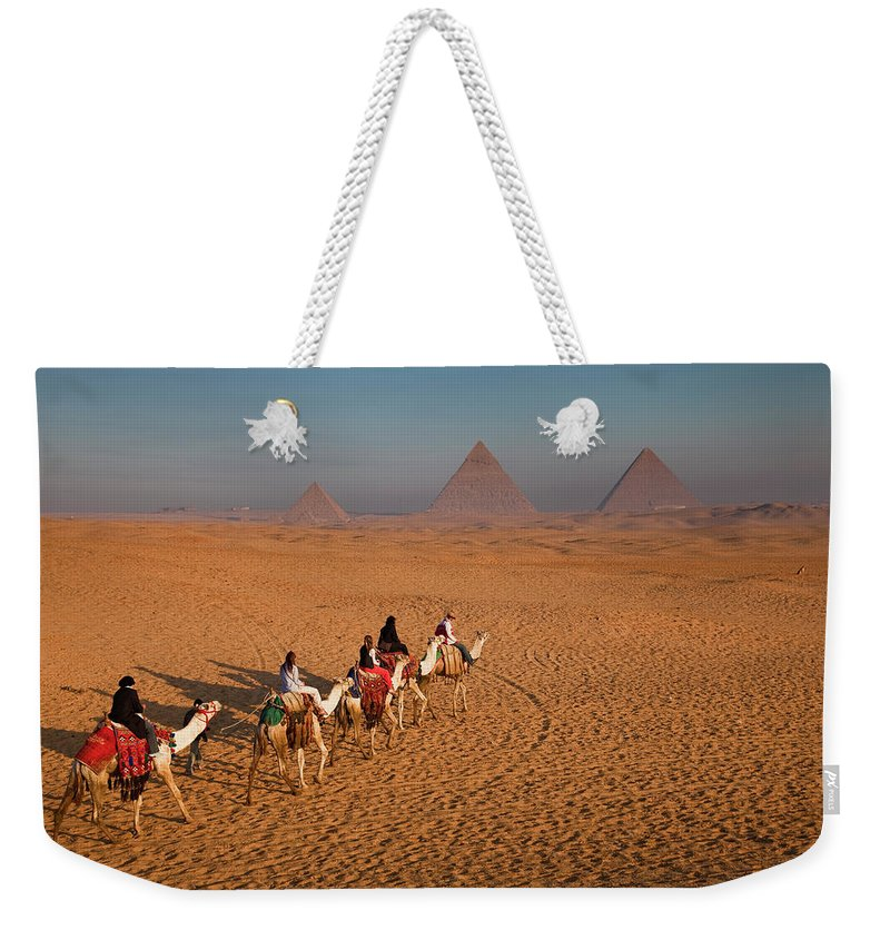 Working Animal Weekender Tote Bag featuring the photograph Tourists On Camels & Pyramids Of Giza by Richard I'anson