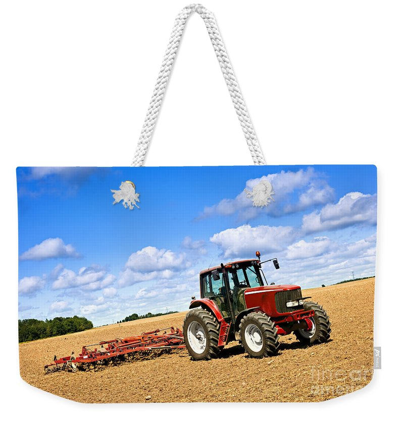 Tractor Weekender Tote Bag featuring the photograph Tractor In Plowed Farm Field by Elena Elisseeva
