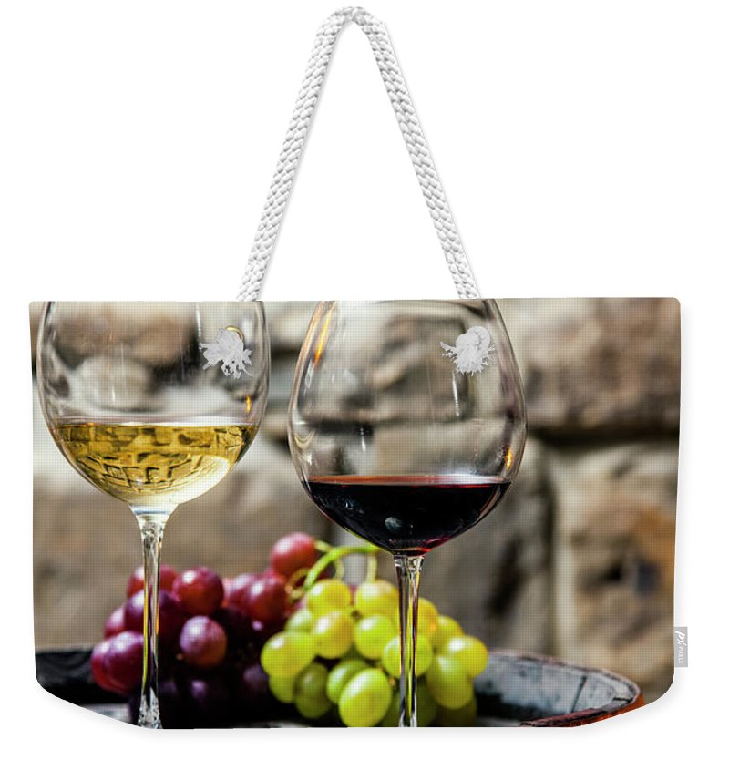Alcohol Weekender Tote Bag featuring the photograph Two Glasses Of Red And White Wine In by Piranka