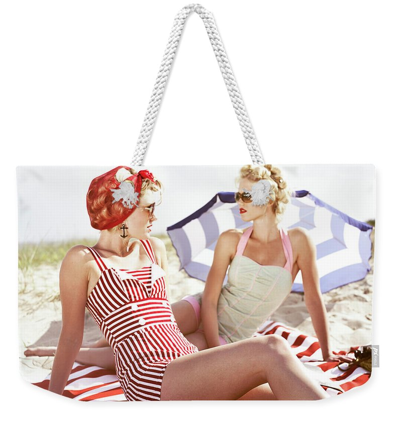 Three Quarter Length Weekender Tote Bag featuring the photograph Two Retro Young Women On Beach by Johner Images