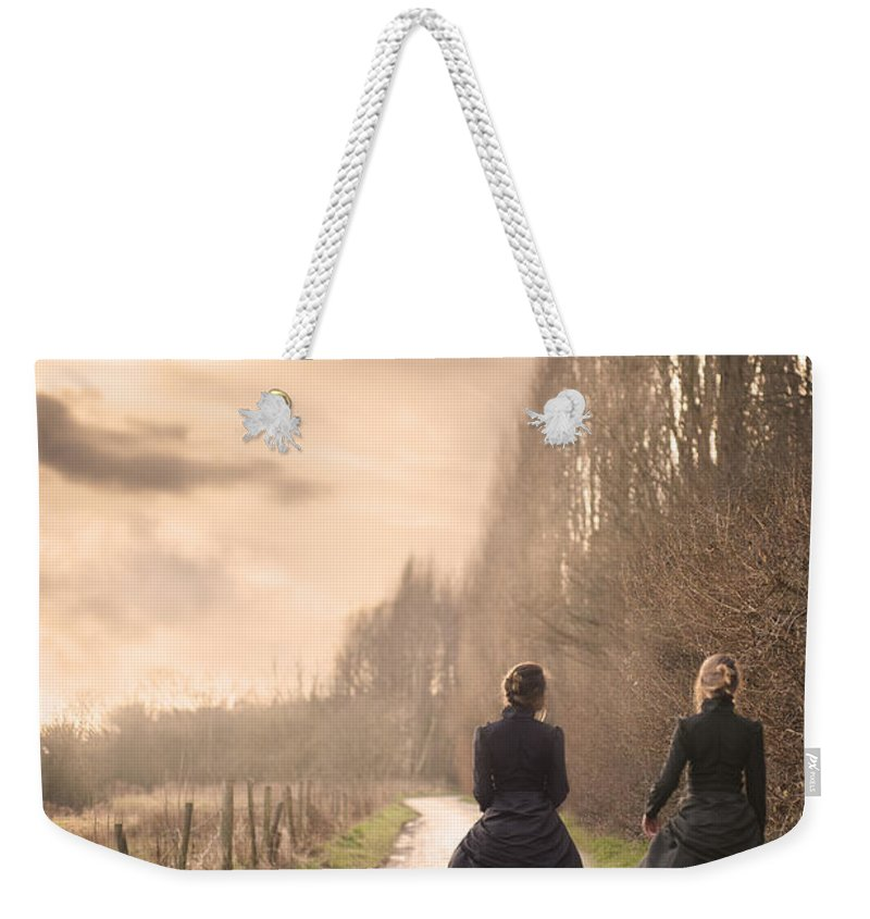 Victorian Weekender Tote Bag featuring the photograph Two Victorian Ladies Walking On A Cobbled Path by Lee Avison
