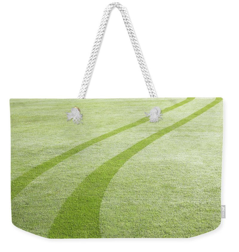 Curve Weekender Tote Bag featuring the photograph Tyre Tracks In Dew by Ezra Bailey