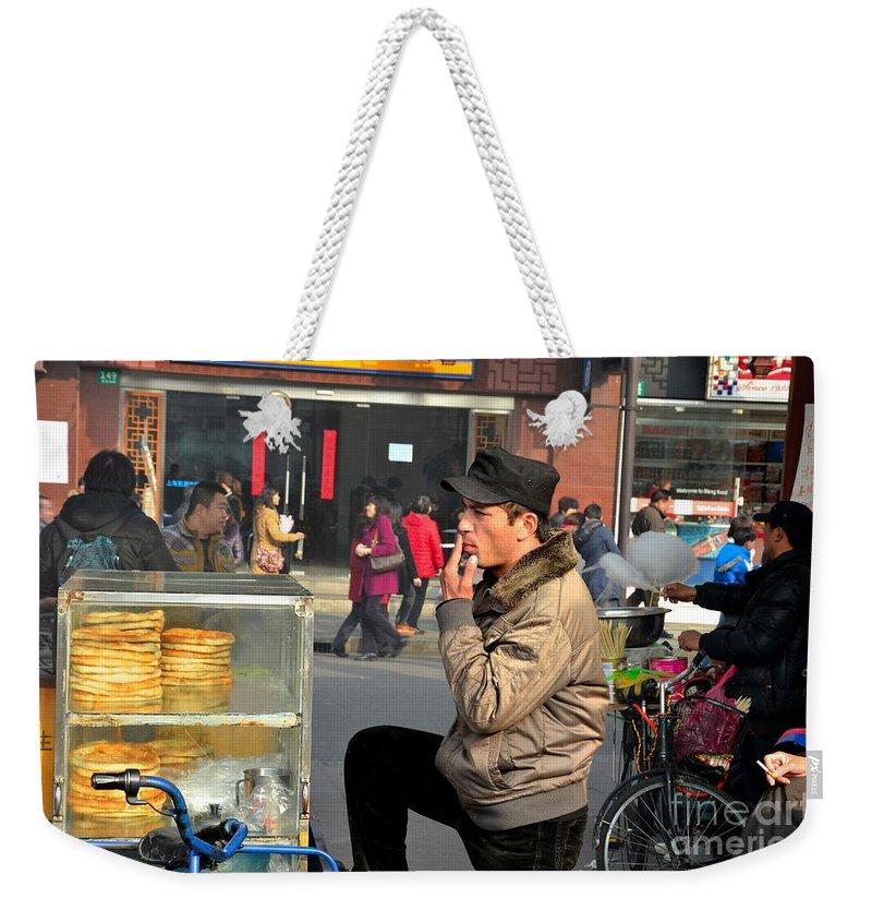 Shanghai Weekender Tote Bag featuring the photograph Uighur Street Side Bread Vendor Smokes Shanghai China by Imran Ahmed