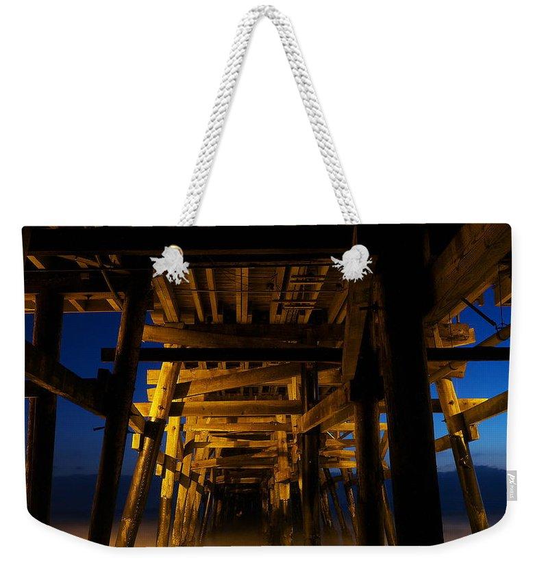 Under The Pier At Night Weekender Tote Bag featuring the photograph Under The Pier At Night by Richard Cheski