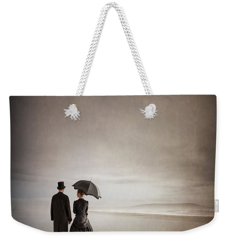 Victorian Weekender Tote Bag featuring the photograph Victorian Couple On The Beach by Lee Avison