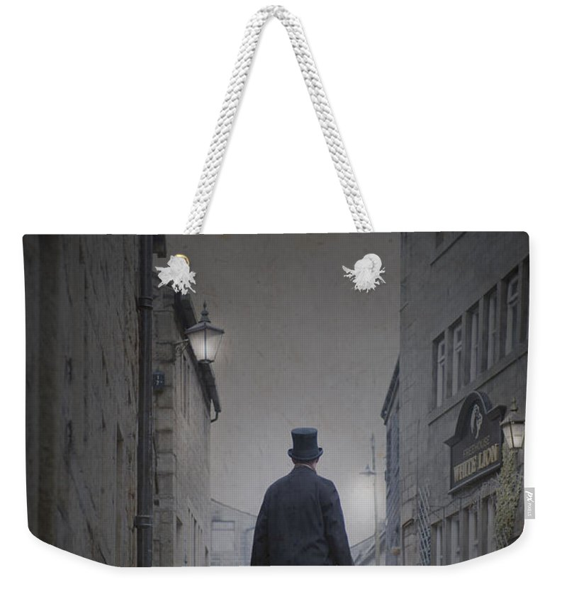 Man Weekender Tote Bag featuring the photograph Victorian Man In Top Hat On A Cobbled Road At Night by Lee Avison