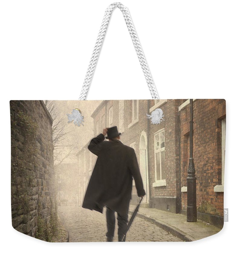 Victorian Weekender Tote Bag featuring the photograph Victorian Man Running On A Cobbled Road by Lee Avison