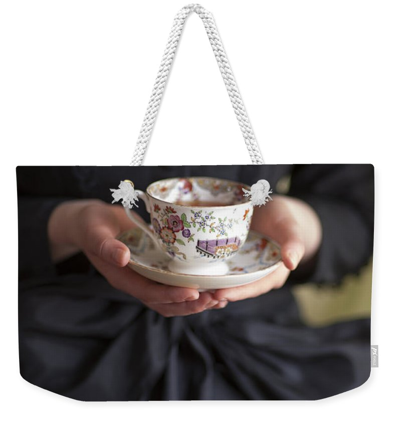Woman Weekender Tote Bag featuring the photograph Victorian Woman Holding A China Cup And Saucer Of Tea by Lee Avison