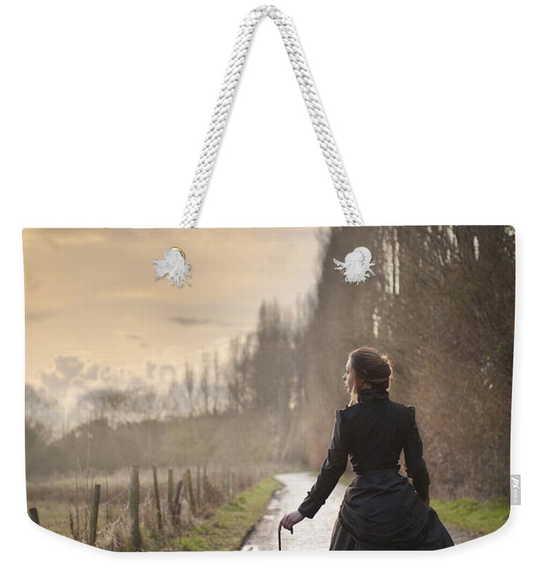 Victorian Weekender Tote Bag featuring the photograph Victorian Woman Walking On A Cobbled Avenue At Sunset by Lee Avison