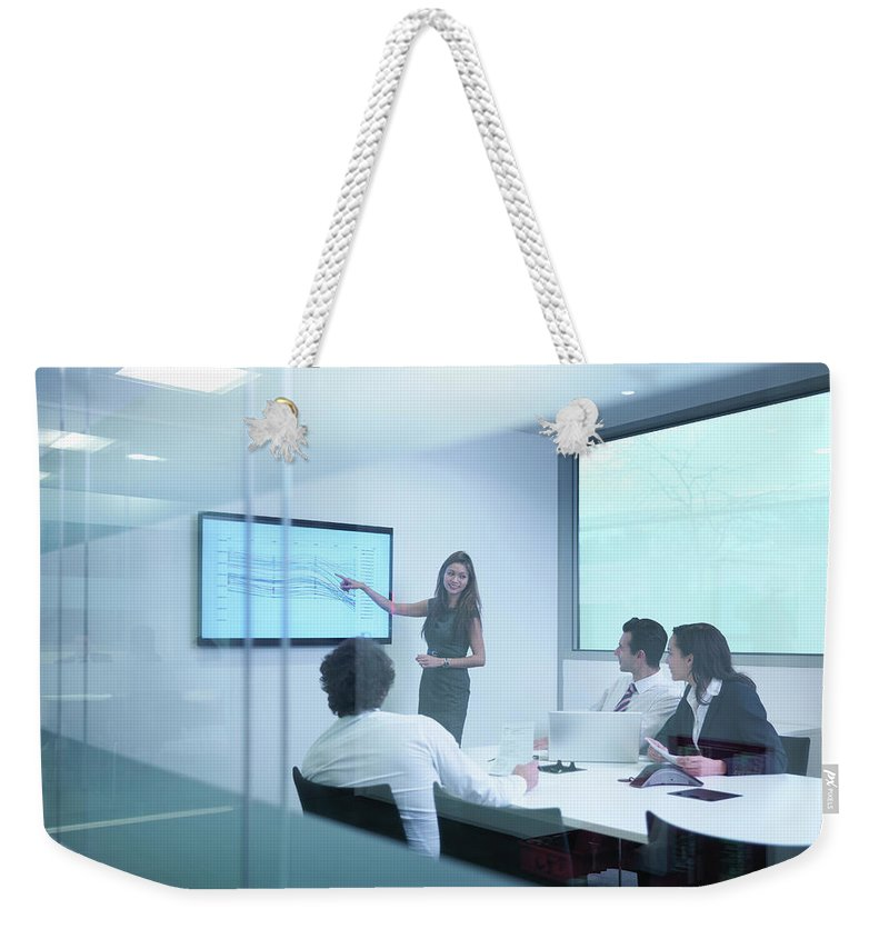 Working Weekender Tote Bag featuring the photograph View Through Glass Wall Of Business by Monty Rakusen