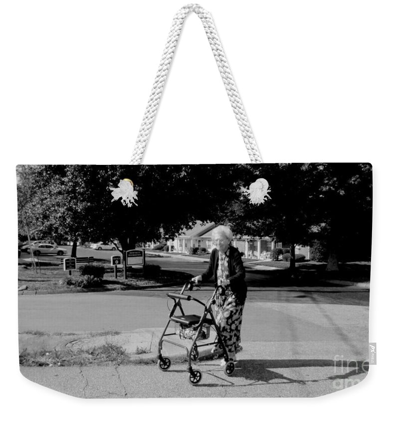A Happy Elderly Woman Walking To The Grocery Store With Her Walker. Weekender Tote Bag featuring the photograph Walker by Robert Loe