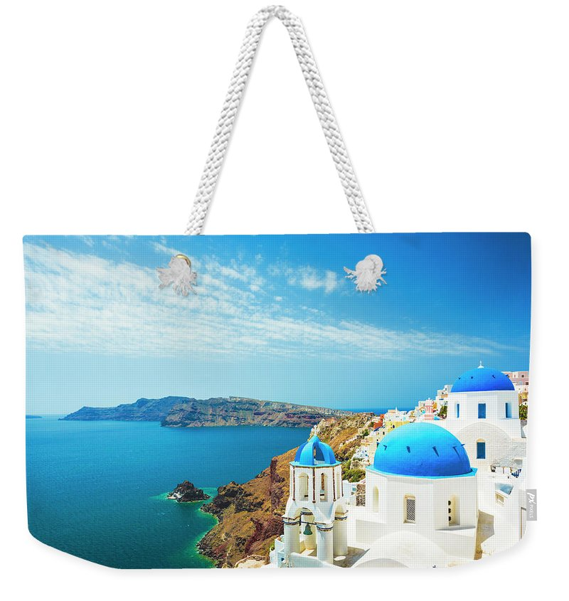 Archipelago Weekender Tote Bag featuring the photograph White Church In Oia Town On Santorini by Spooh