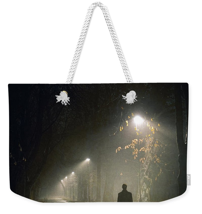 Woman Weekender Tote Bag featuring the photograph Woman Alone On A Park Avenue by Lee Avison