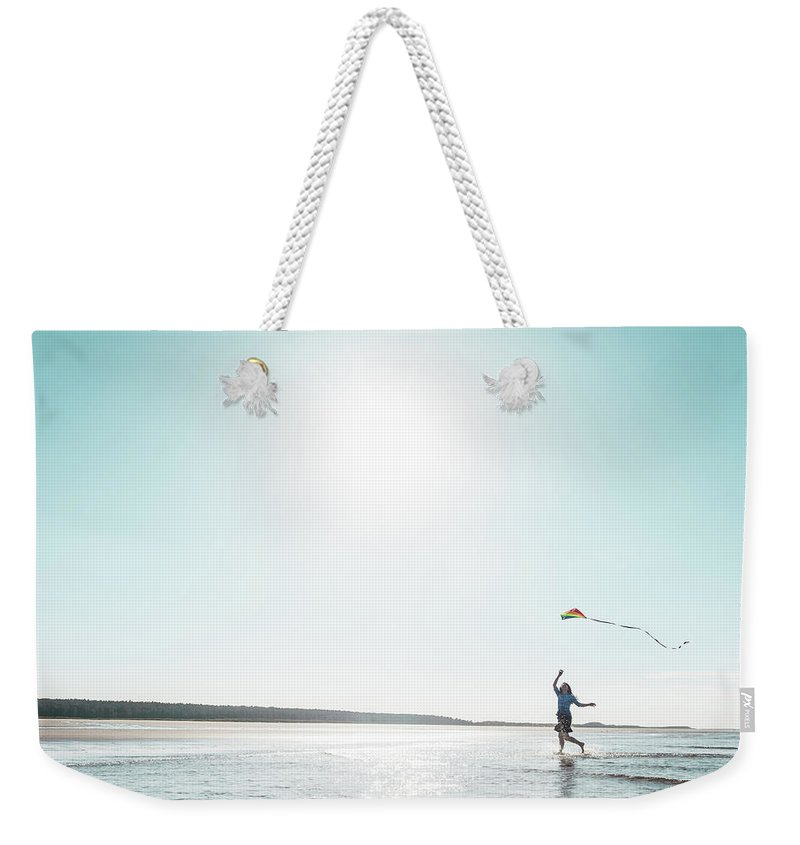 Three Quarter Length Weekender Tote Bag featuring the photograph Woman Flying Kite On Beach by Dan Brownsword