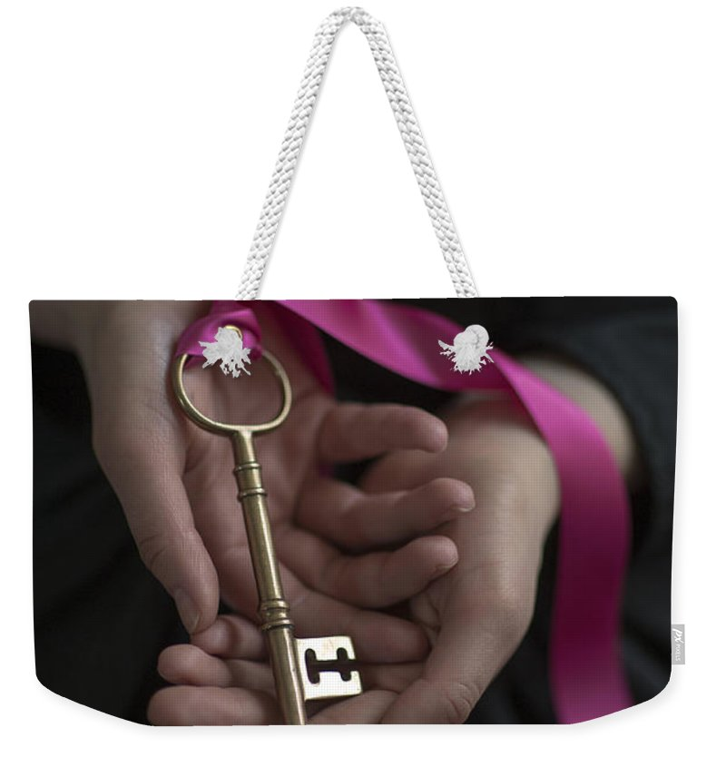 Woman Weekender Tote Bag featuring the photograph Woman Holding A Golden Key On A Pink Ribbon by Lee Avison