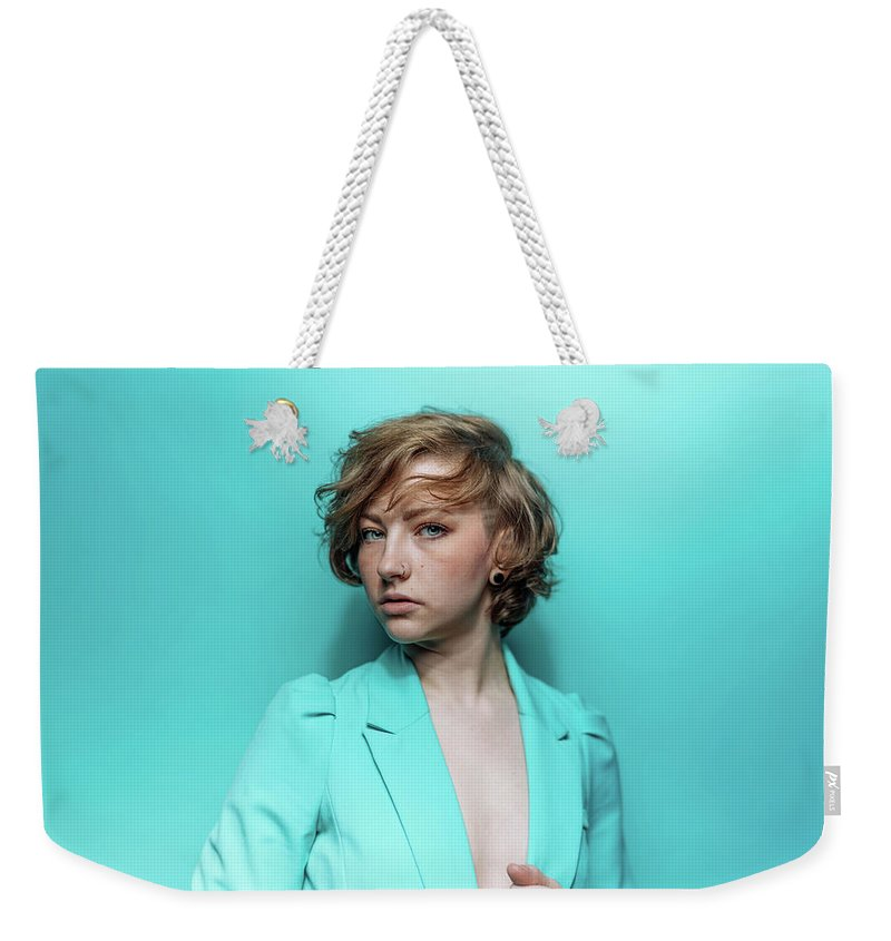 People Weekender Tote Bag featuring the photograph Woman In Blue Jacket On Blue Background by Ian Ross Pettigrew