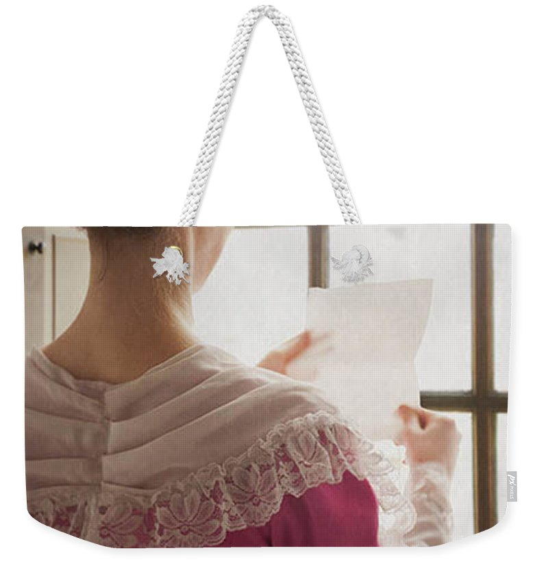 Woman Weekender Tote Bag featuring the photograph Woman In Historical Costume Reading A Letter By The Window by Lee Avison
