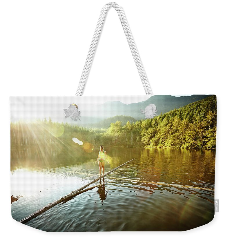 Pets Weekender Tote Bag featuring the photograph Woman Walking On Log In Alpine Lake by Thomas Barwick