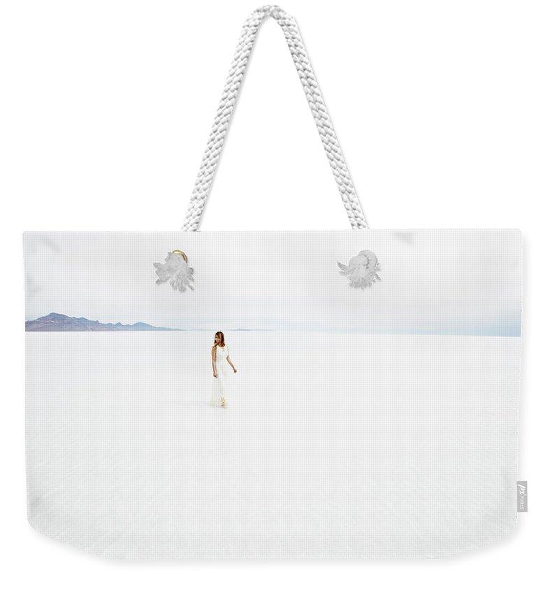 Scenics Weekender Tote Bag featuring the photograph Woman Wearing Dress Walking Through by Thomas Barwick