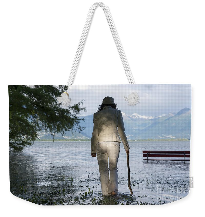 Woman Weekender Tote Bag featuring the photograph Woman With A Stick by Mats Silvan