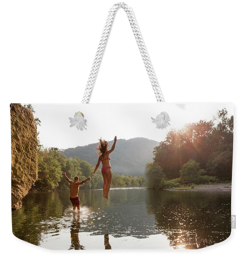 Young Men Weekender Tote Bag featuring the photograph Young Couple Jumping Into River by Zave Smith