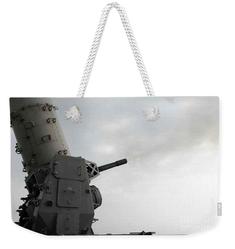 Uss Makin Island Weekender Tote Bag featuring the photograph A Close-in Weapons System Is Fired by Stocktrek Images