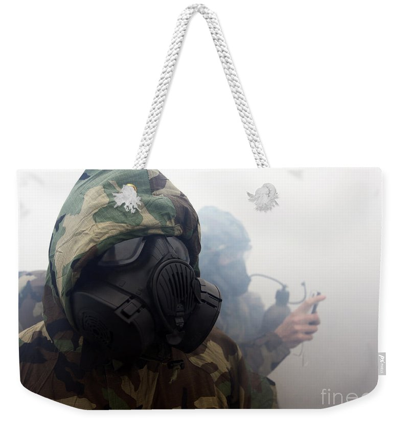 Us Marine Corps Weekender Tote Bag featuring the photograph A Marine Wearing A Gas Mask by Stocktrek Images