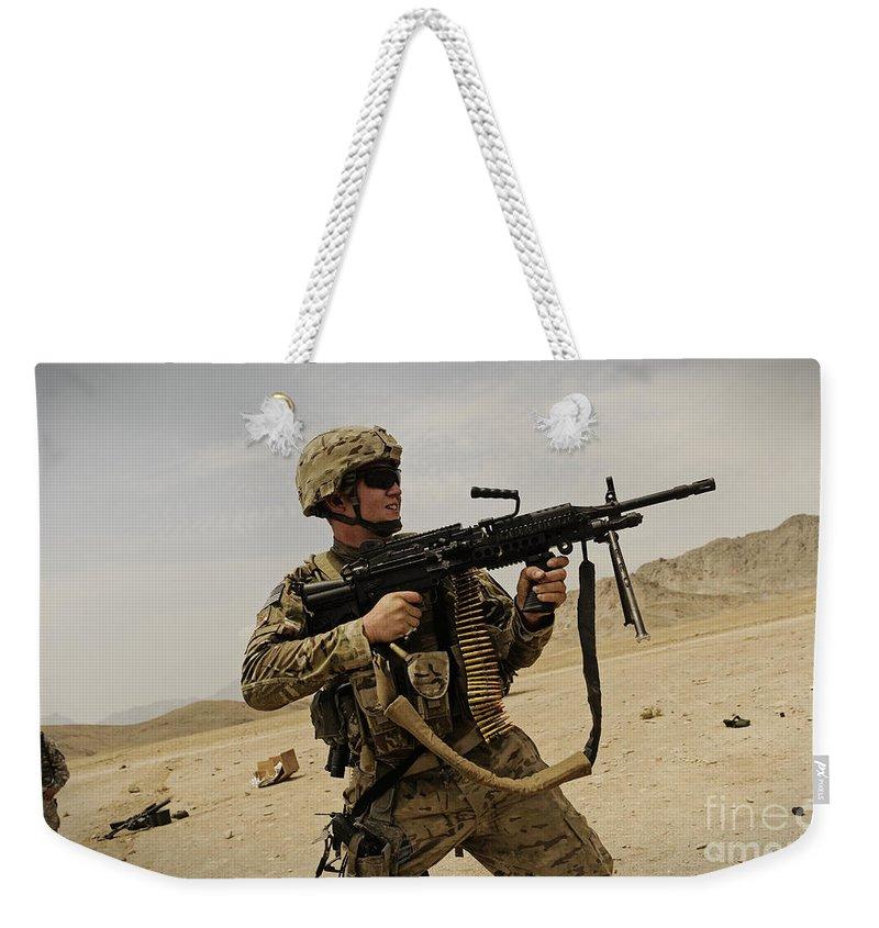 Army Weekender Tote Bag featuring the photograph A Soldier Firing His Mk-48 Machine Gun by Stocktrek Images