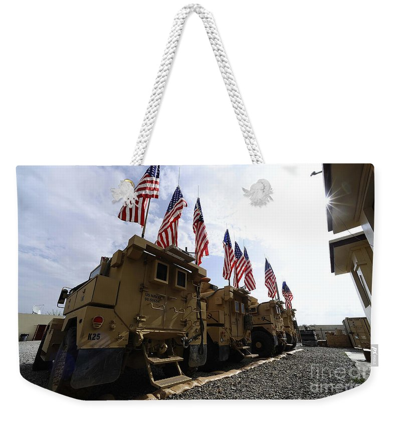 Tactical Weekender Tote Bag featuring the photograph American Flags Are Displayed by Stocktrek Images