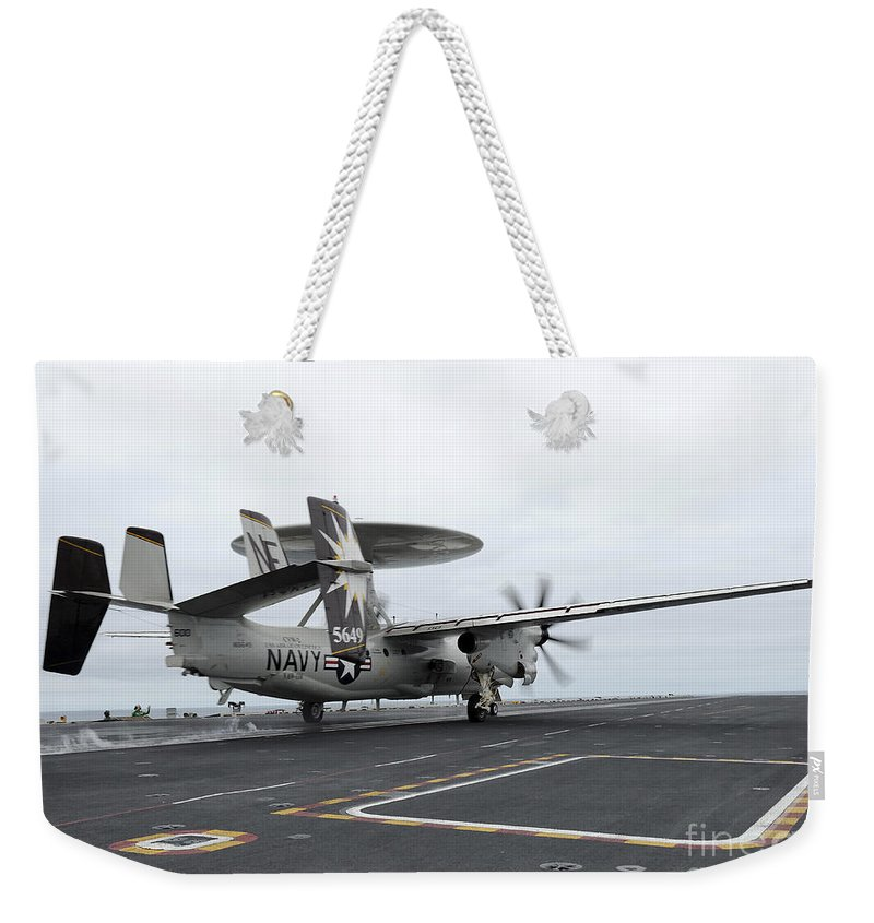 Uss Abraham Lincoln Weekender Tote Bag featuring the photograph An E-2c Hawkeye Launches Off The Flight by Stocktrek Images
