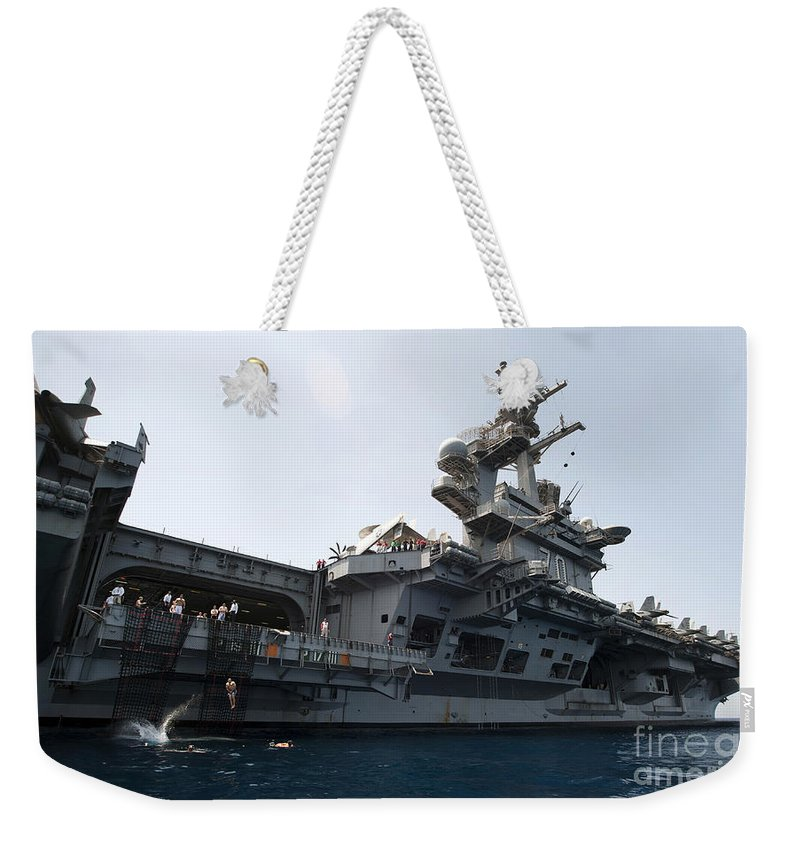 Uss Carl Vinson Weekender Tote Bag featuring the photograph Sailors Jump To The Sea During A Swim by Stocktrek Images
