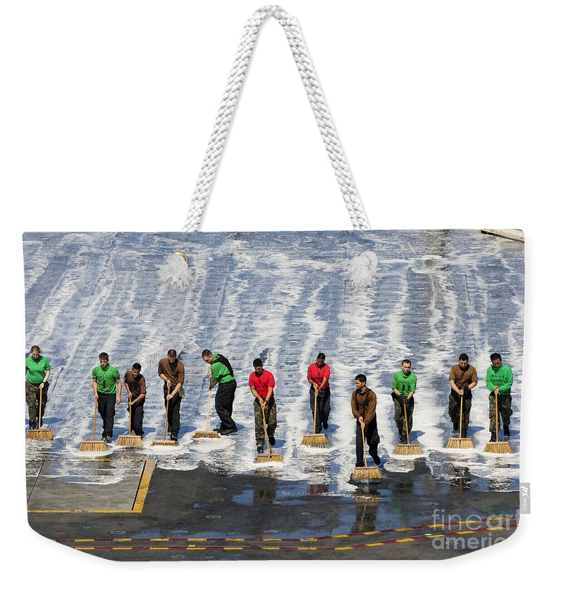 Maintenance Weekender Tote Bag featuring the photograph Sailors Perform A Flight Deck Wash by Stocktrek Images