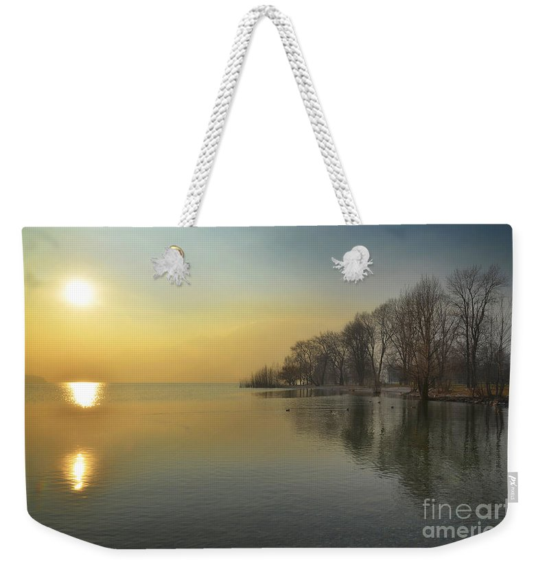 Sunshine Weekender Tote Bag featuring the photograph Sunshine Over A Lake by Mats Silvan