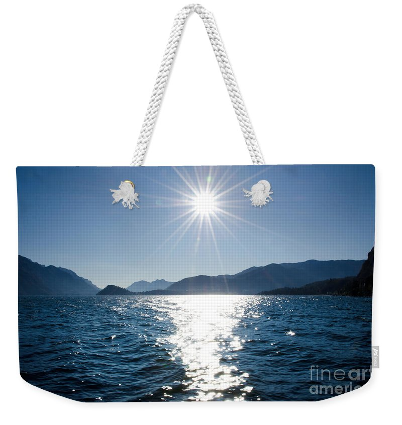 Lake Weekender Tote Bag featuring the photograph Sunshine Over An Alpine Lake by Mats Silvan