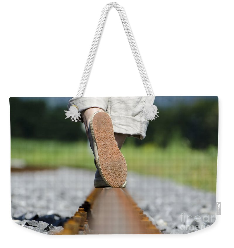 Shoes Weekender Tote Bag featuring the photograph Walking On Railroad Tracks by Mats Silvan