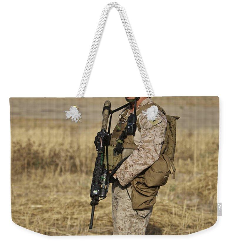 Field Weekender Tote Bag featuring the photograph U.s. Marine Patrols A Wadi Near Kunduz by Terry Moore