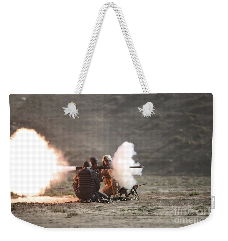 Afghan National Police Weekender Tote Bag featuring the photograph An Afghan Police Studen Fires by Terry Moore