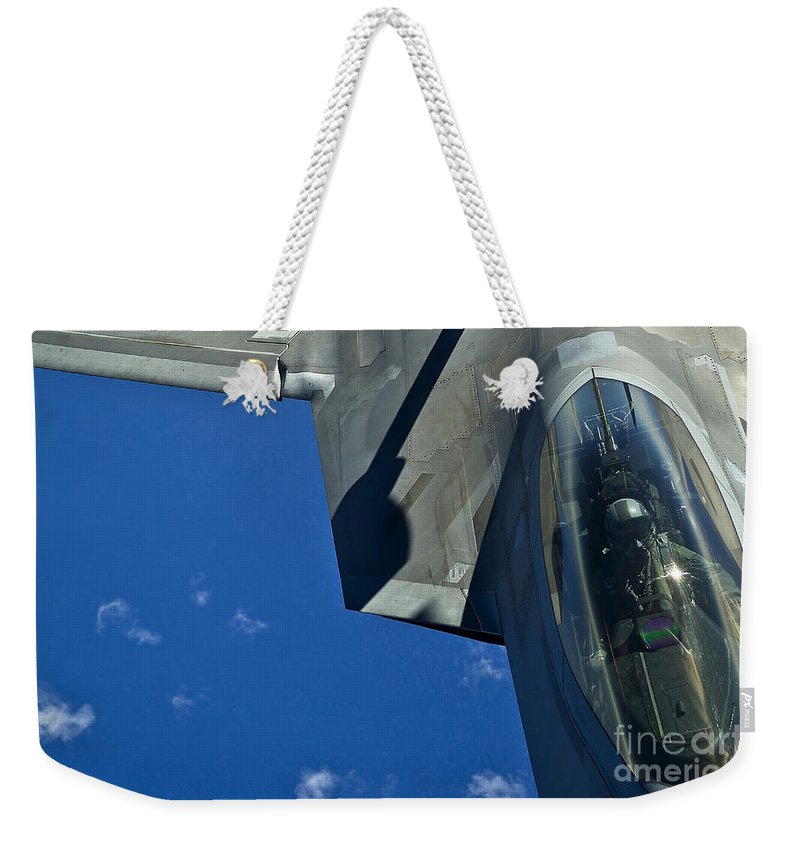Military Weekender Tote Bag featuring the photograph An F-22 Raptor In Flight by Stocktrek Images
