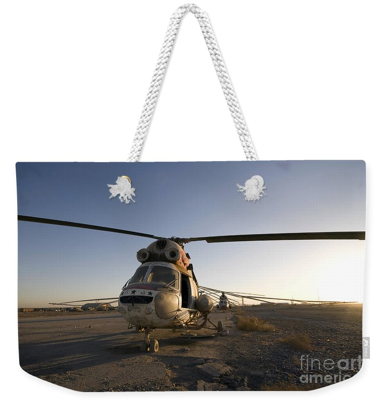 Aviation Weekender Tote Bag featuring the photograph An Iraqi Helicopter Sits On The Flight by Terry Moore