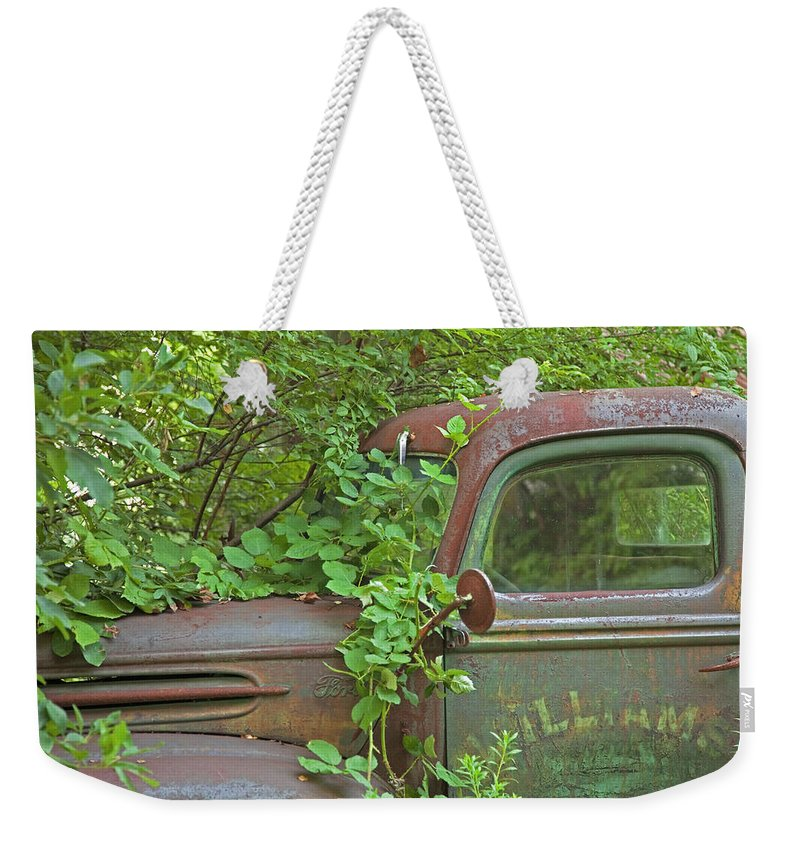 Rustbuckets Weekender Tote Bag featuring the photograph Overgrown Rusty Ford Pickup Truck by John Stephens
