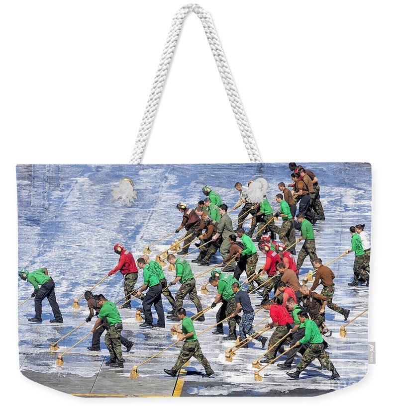 Walking Weekender Tote Bag featuring the photograph Sailors Perform A Flight Deck Wash by Stocktrek Images