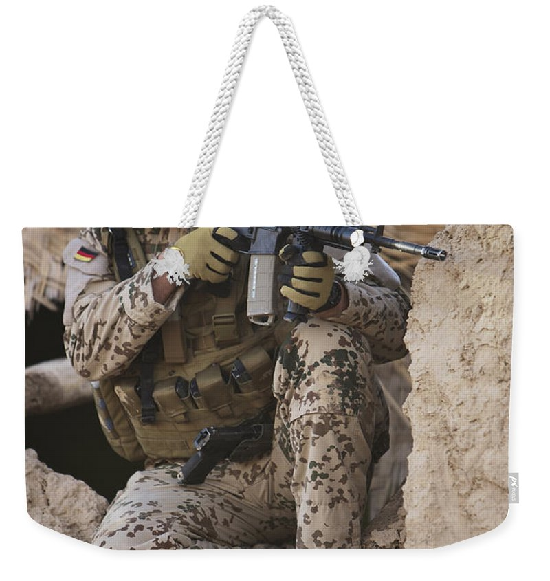 Sitting Weekender Tote Bag featuring the photograph A German Army Soldier Armed With A M4 by Terry Moore