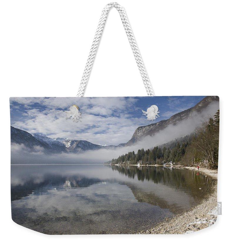 Bohinj Weekender Tote Bag featuring the photograph mist burning off Lake Bohinj by Ian Middleton