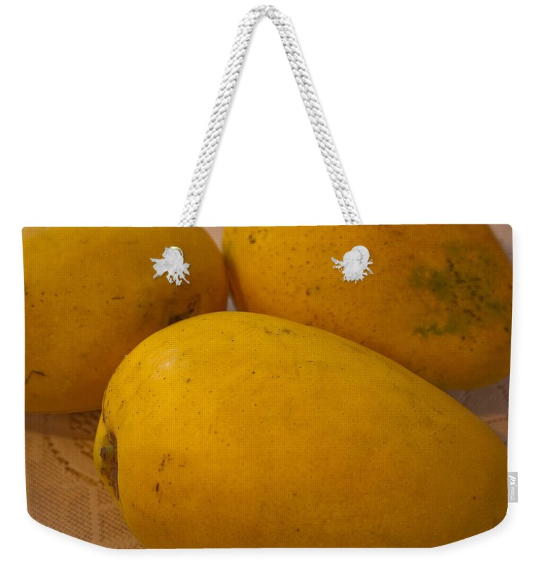 Yellow Weekender Tote Bag featuring the photograph 3 Yellow And Luscious Mangos On A White Sheet by Ashish Agarwal