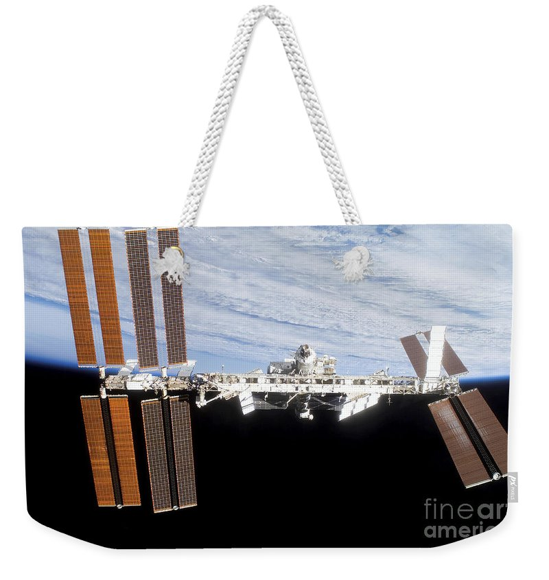 Blue Weekender Tote Bag featuring the photograph International Space Station by Stocktrek Images