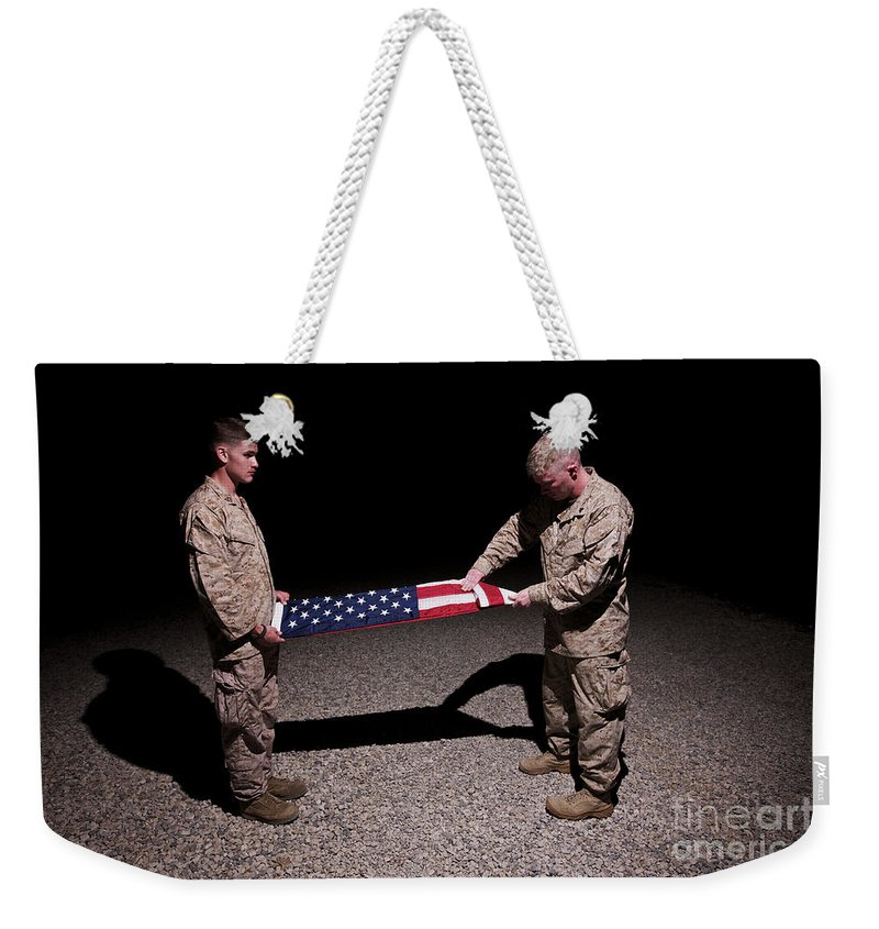 Night Weekender Tote Bag featuring the photograph U.s. Marines Fold The American Flag by Terry Moore