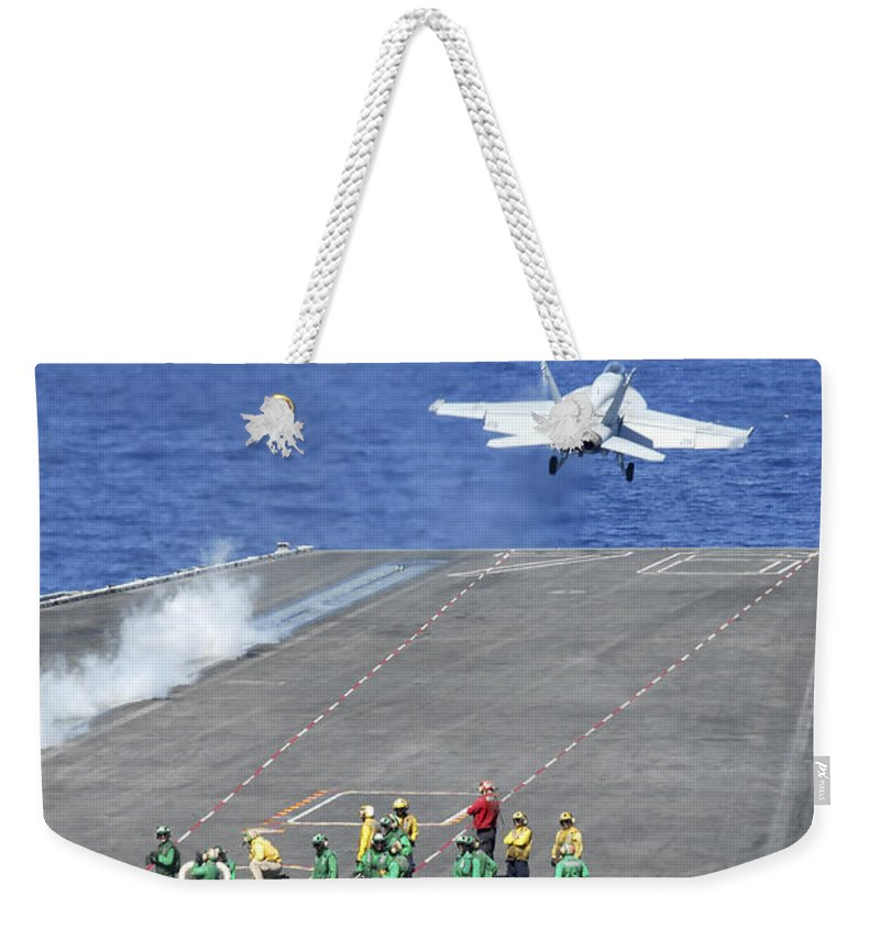 Flight Deck Weekender Tote Bag featuring the photograph An Fa-18e Super Hornet Launches by Stocktrek Images