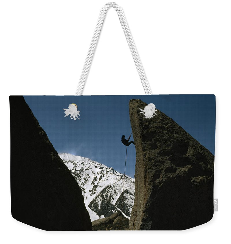 Color Image Weekender Tote Bag featuring the photograph A Climber Rappels Off Grandma Boulder by Gordon Wiltsie