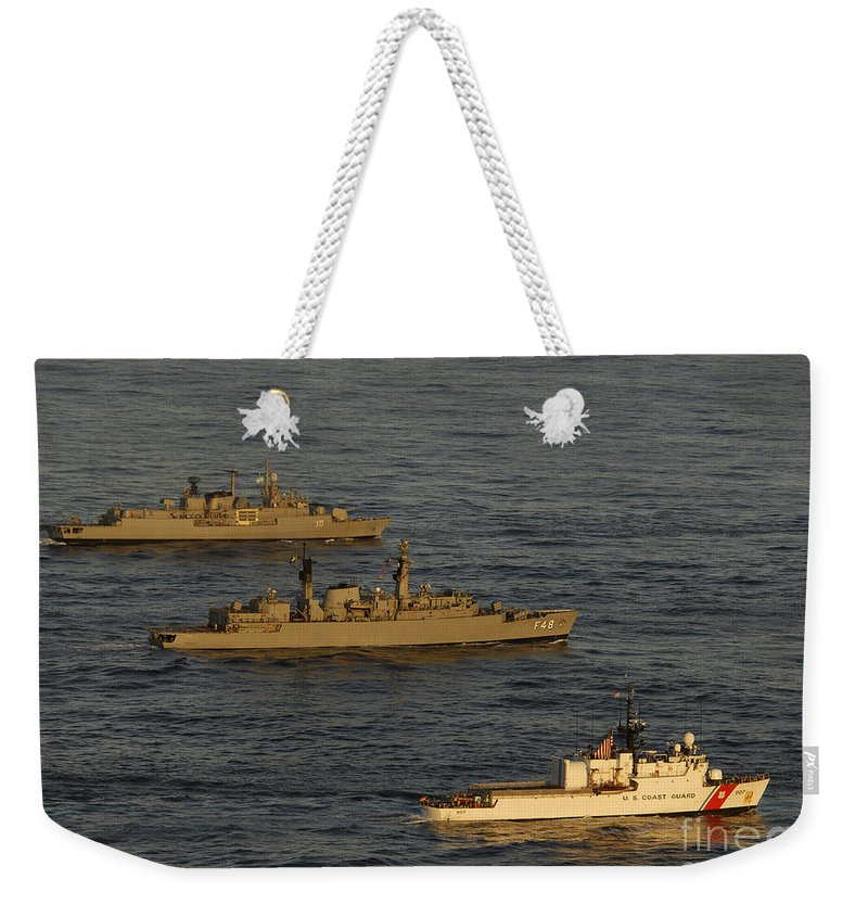 Us Coast Guard Weekender Tote Bag featuring the photograph A Convoy Of Naval Ships Move by Stocktrek Images
