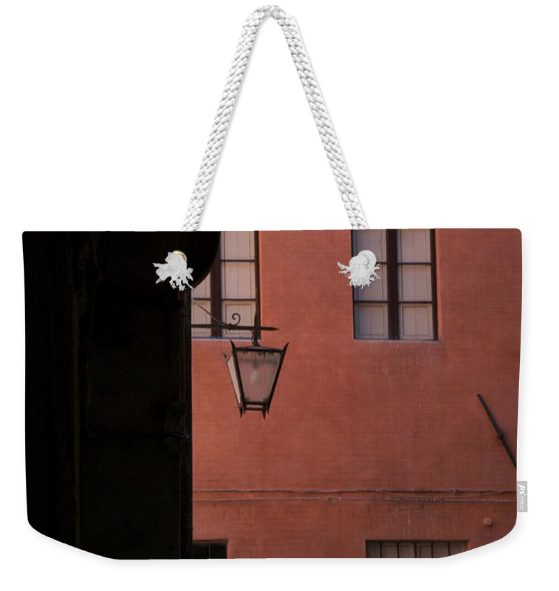 History Weekender Tote Bag featuring the photograph A Dark Alley Way Leads To A Lit Brick by Heather Perry